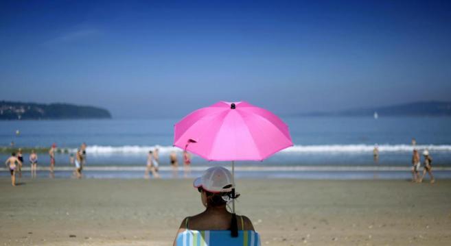 Bañistas disfrutando este lunes del buen tiempo en la playa Grande de...
