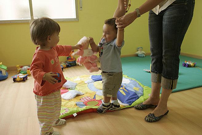 Unos niños juegan con la supervisión de una cuidadora.
