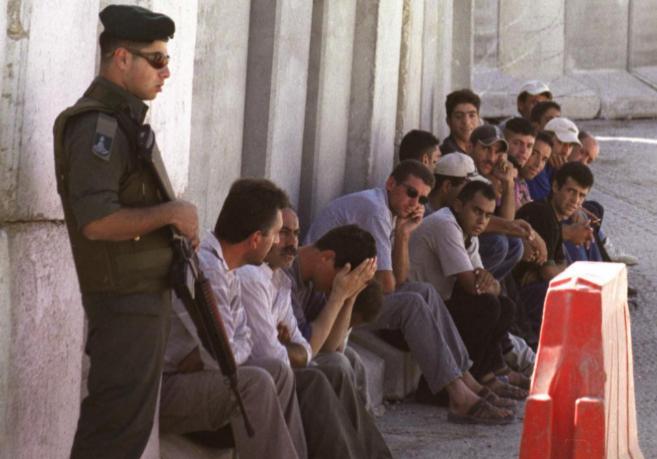 Un soldado israelí vigila a un grupo de hombres palestinos en Abu...