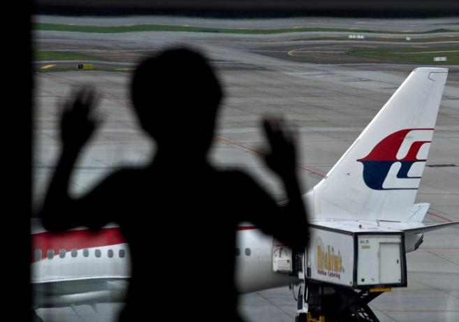 Un niño observa un avión de Malaysia Airlines.
