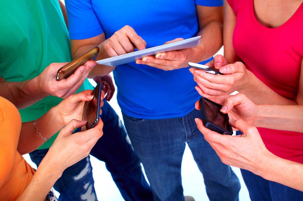 Un grupo de adolescentes usan sus dispositivos tecnológicos.
