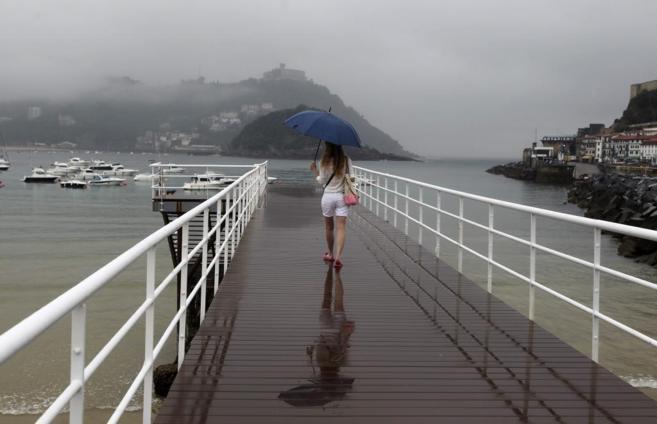 Una joven paseando bajo la lluvia en el Club Náutico de San...