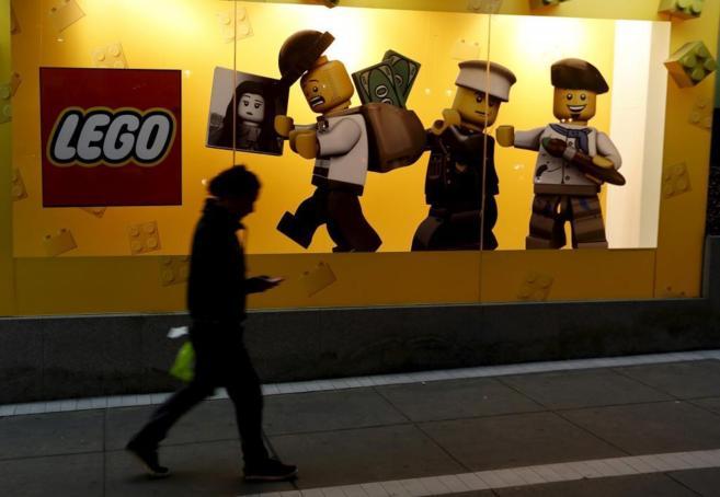 Una mujer camina delante de una tienda de Lego en Lima.