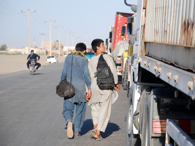 Dos jóvenes afganos deambulan por Zaranj después de haber sido...