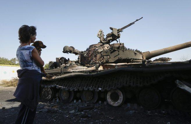Una mujer observa un tanque quemado en la localidad ucraniana de...