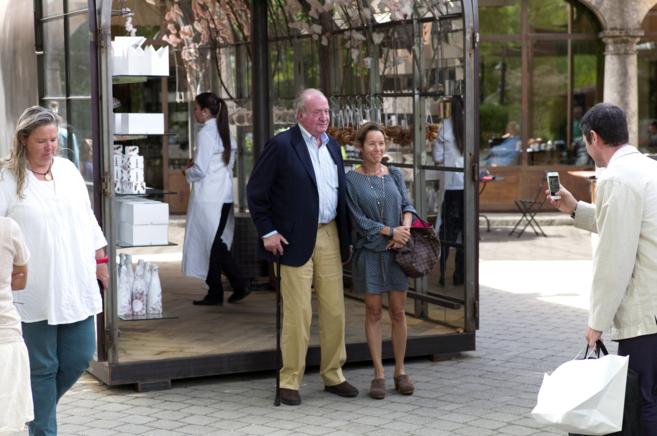 Don Juan Carlos se fotografía con una mujer a la salida de la tienda.