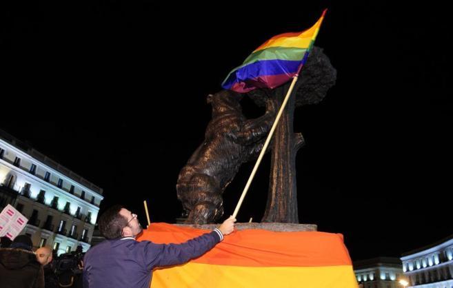Un manifestante envuelve con la bandera arcoiris el Oso y el Madroño...