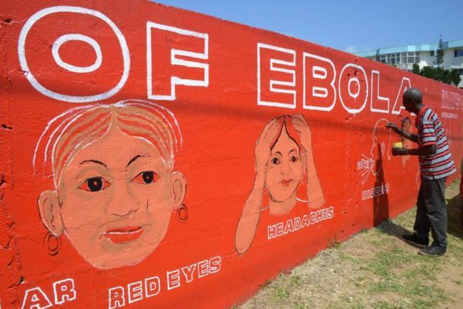 Un artista local de Liberia pinta en una pared los síntomas al inicio...