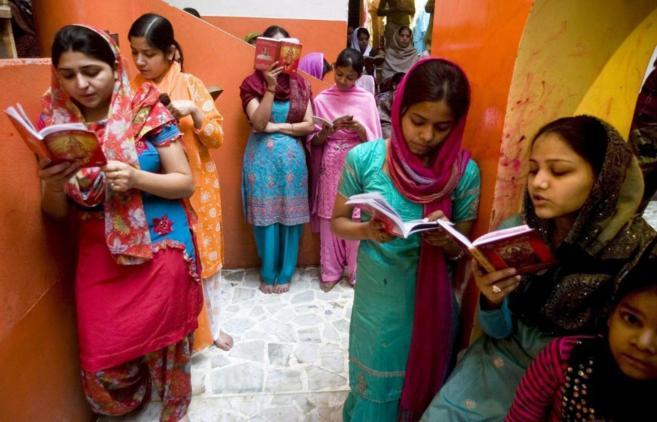 Niñas hindúes leen libros sagrados durante el Festival de Navratri...