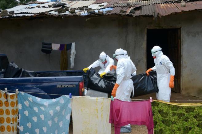 Sanitarios de la Cruz Roja trasladan el cuerpo de una víctima por...