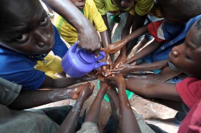 Un grupo de jóvenes se lava las manos con agua y lejía para prevenir...