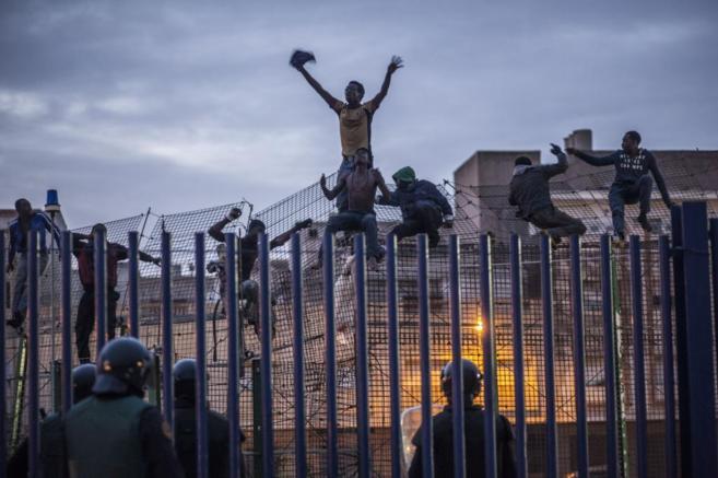 Un grupo de inmigrantes subidos en la valla que separa Marruecos de...