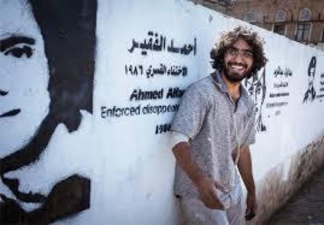 El joven posa junto a uno de sus murales en Saná.