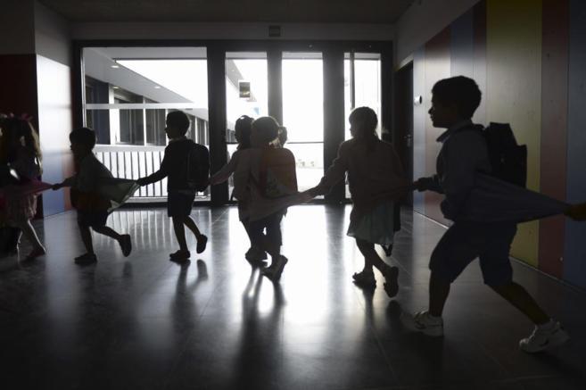 Varios niños se dirigen a su clase el primer día del curso escolar...