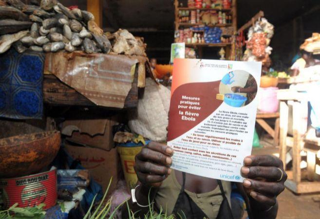 Una mujer senegalesa sostiene un cartel con medidas de prevención...