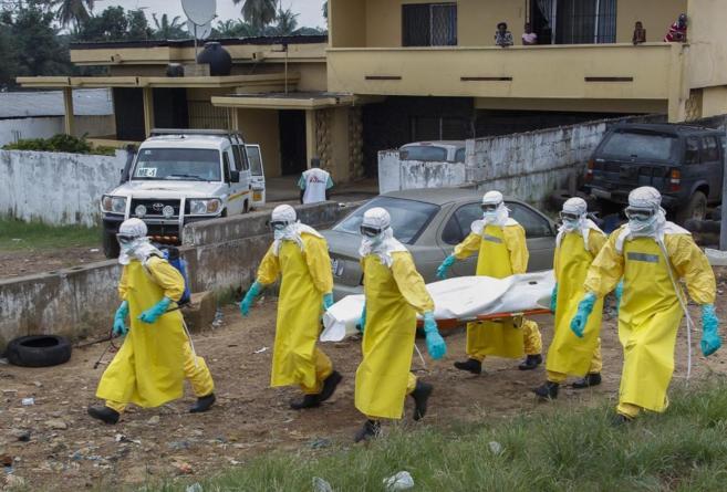 Varios especialistas de la salud transportan el cuerpo sin vida de una...