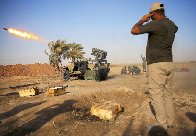 Milicianos chiíes lanzan cohetes durante duros enfrentamientos contra...
