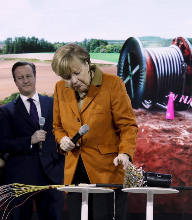 La canciller alemana, Angela Merkel, examina fibra y cables...