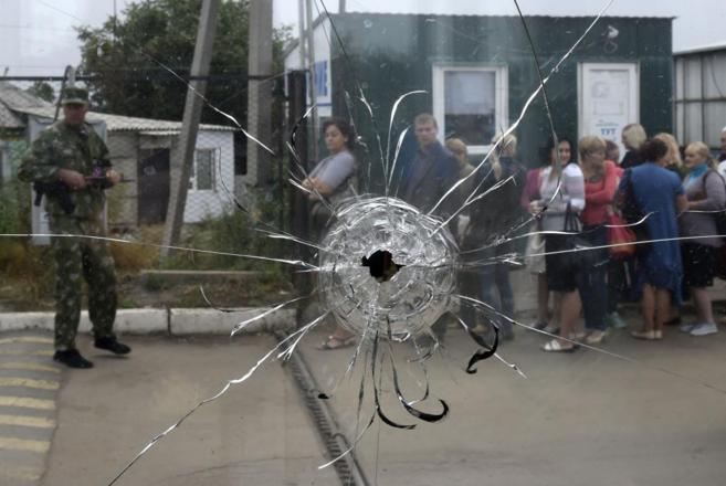 Ucranianos, vistos a través de un cristal roto, hacen cola en...