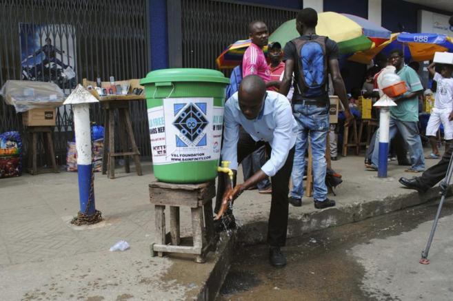 Un hombre se lava las manos como medida preventiva. (Monrovia,...