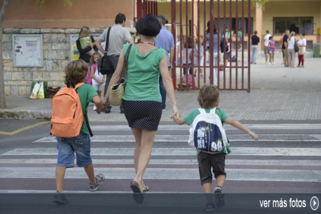Una madre lleva a sus hijos al colegio con las camisetas de Crida.
