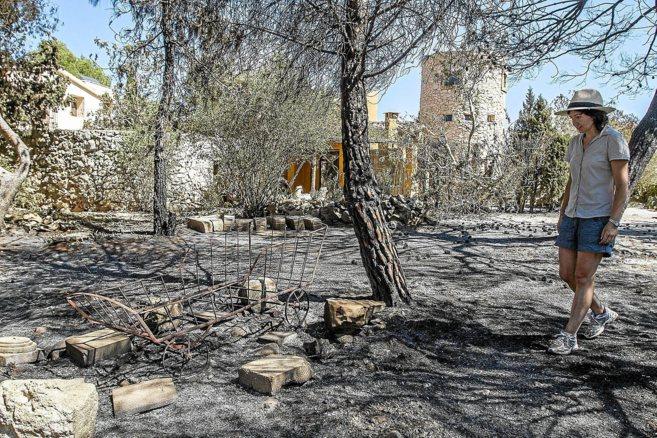 Una mujer observa los daños ocasionados por el incendio en las...