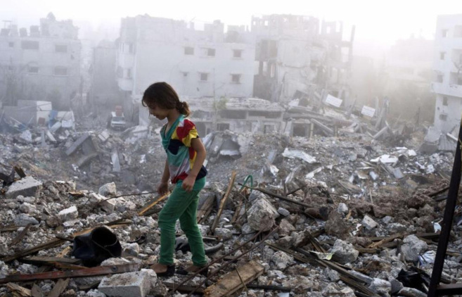 Una niña camina sobre los escombros de lo que antes era su casa.