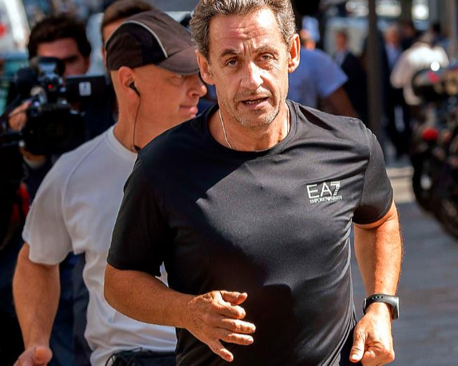 El ex presidente francés Nicolas Sarkozy corre por las calles de...