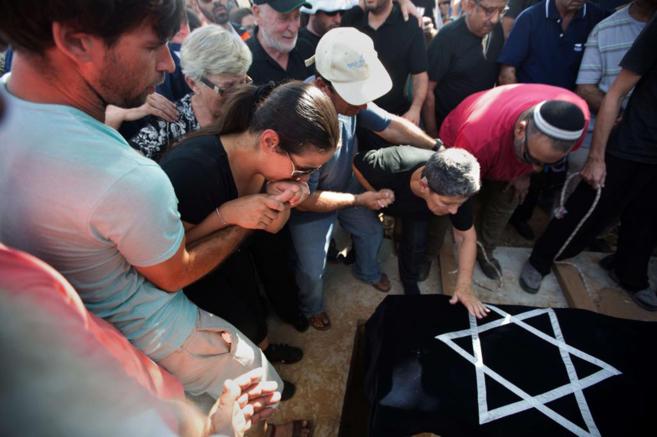 Los padres de un joven asesinado en un ataque palestino lloran ante su...