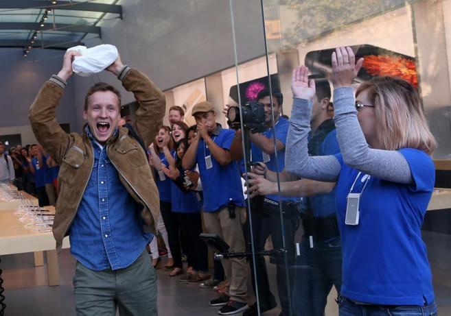 Un cliente es vitoreado mientras sale del Apple Store de Palo Alto con...