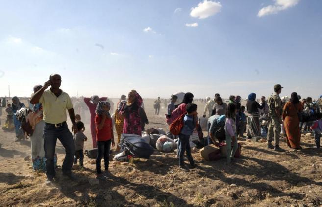 Refugiados sirios esperan en el paso fronterizo con Turquía de...