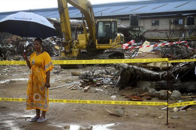 Mujer ante escombros por el derrumbe de un edificio