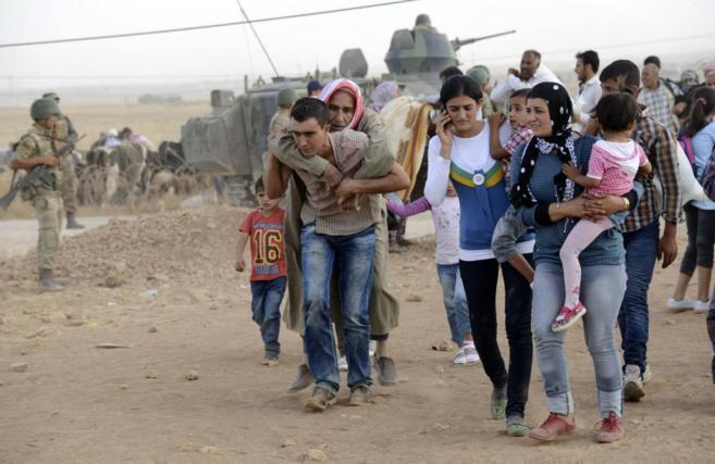 Cientos de kurdos cruzan la frontera entre Turquía y Siria, cerca de...