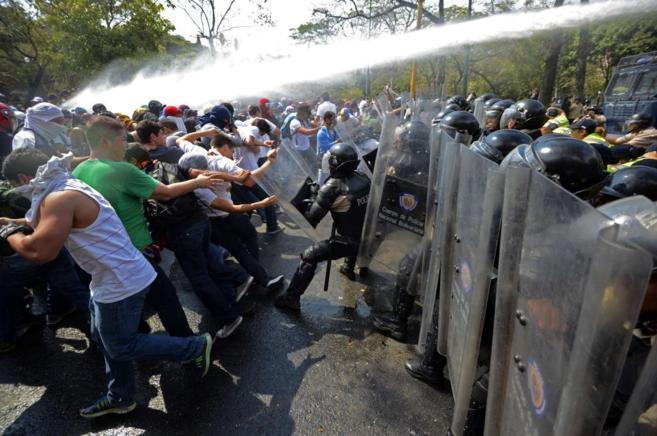 Estudiantes venezolanos se enfrentan a la policía durante protestas...