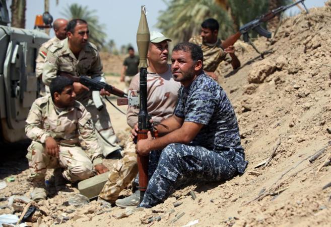 Soldados iraquíes y suníes toman posiciones en las afueras de la...