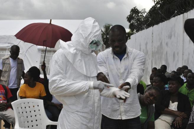 Un voluntario toma medidas para evitar contagiarse en Monrovia,...
