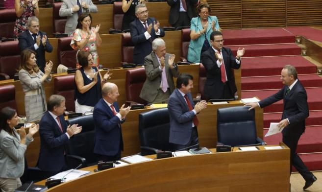 Alberto Fabra se dirige a su escaño, aplaudido por los diputados del...