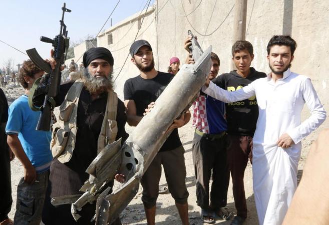 Militantes del Estado Islámico, con un casquillo de misil en Raqqa,...