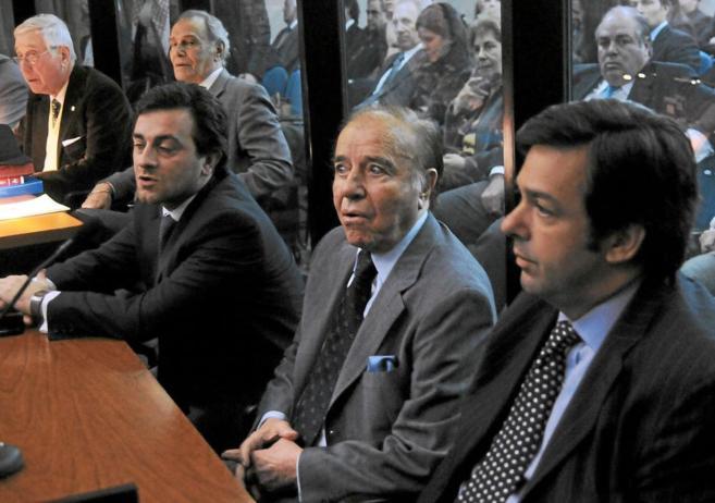 Carlos Menem, en el centro, escucha la lectura de su sentencia en...