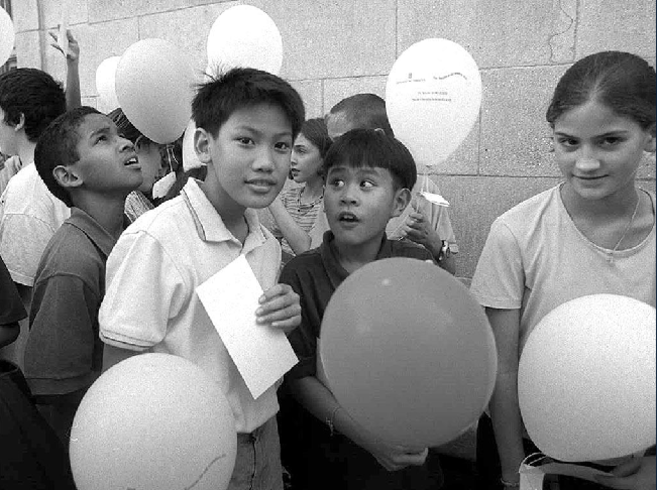 Un grupo de niños disfruta de unos globos regalados en la edición...