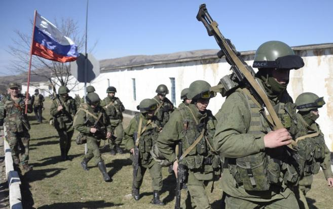 Un militar con una bandera rusa, junto con otros militares, intentan...