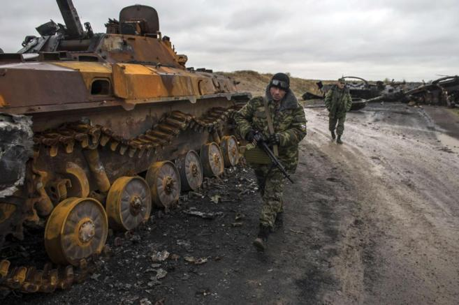 Dos rebeldes caminan al lado de un carro de combate calcinado en...