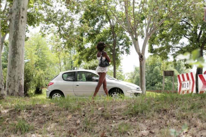 Una prostituta delante de un coche