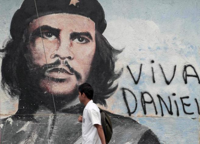 Un estudiante pasa junto a un mural del Che Guevara en Managua...