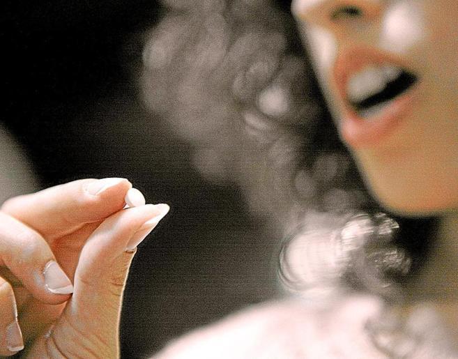 Una mujer tomando una píldora anticonceptiva.
