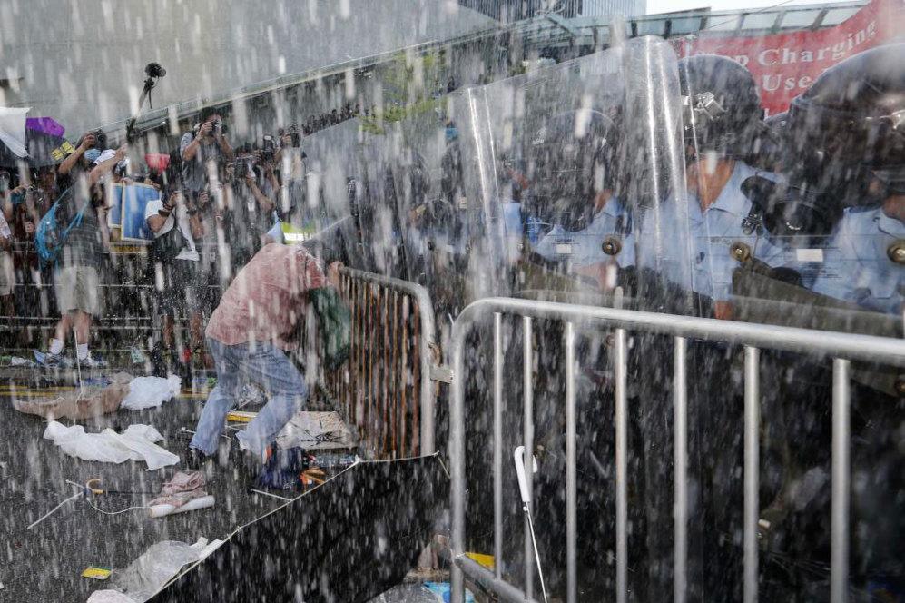 Un manifestante se resiste a abandonar y se aferra a una valla...