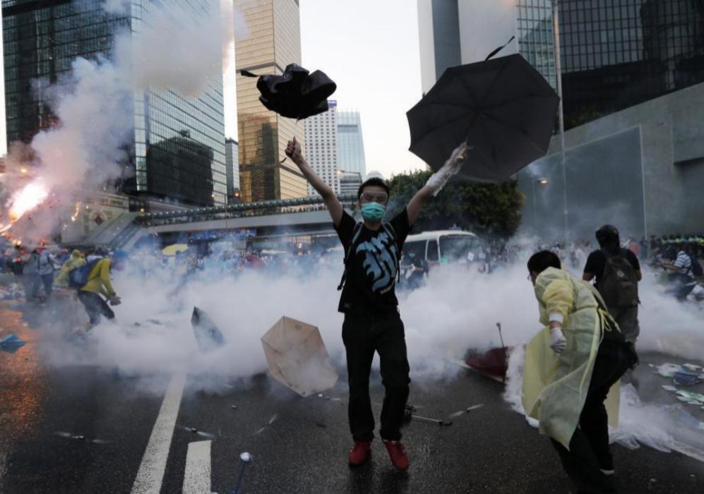 Un manifestante levanta sus paraguas delante del gas lacrimógeno que...