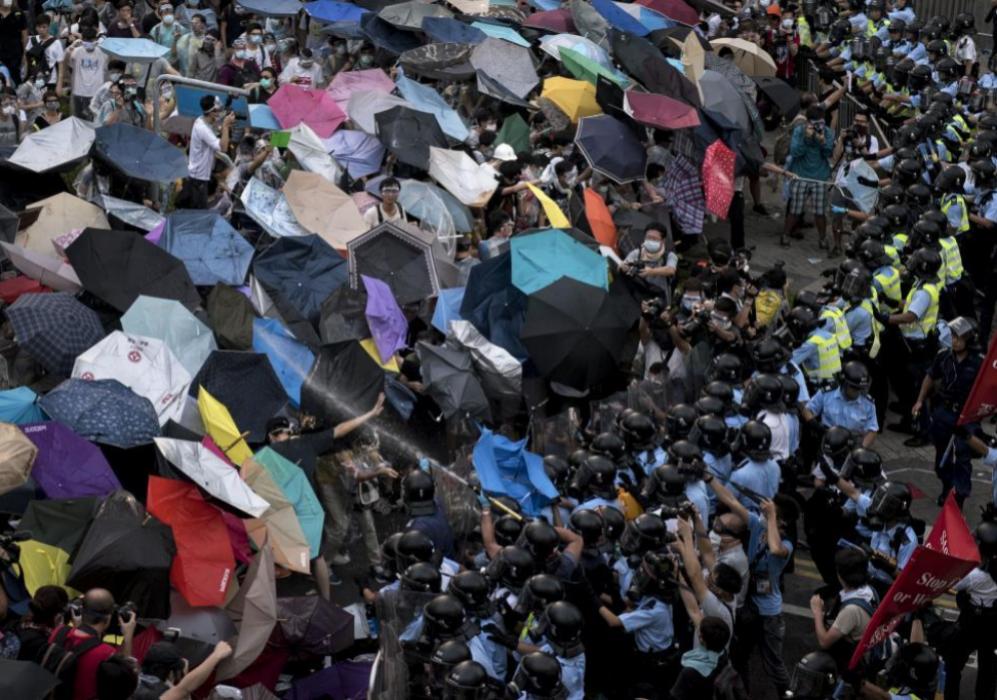 Los manifestantes se cubren con paraguas ante el gas que lanzan las...