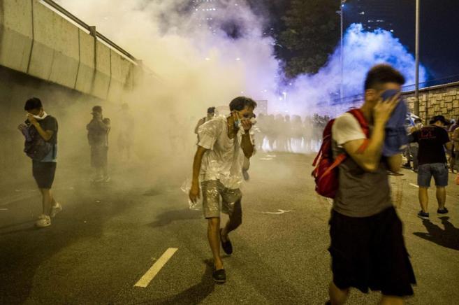 Los manifestantes intentan ocultarse de los gases lacrimógenos.