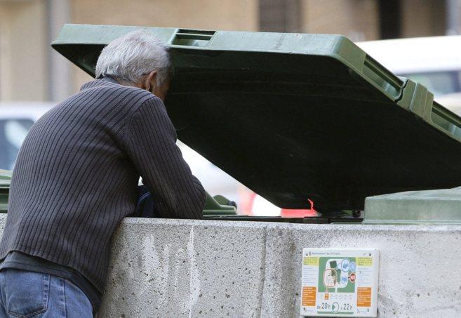 Una persona buscando en un contenedor de basura en Valencia.